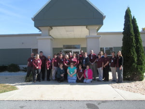 """PMH  staff and board members pose in front of the 20-year-old """"new"""" hospital during the birthday celebration."""