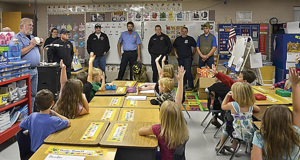 KiNdergarten students at Green Bank Elementary-Middle School listen as members of Bartow-Frank-Durbin fire and rescue department explain how important it is to have a smoke detector in their home and bedroom. From left, Assistant Fire Chief Dennis Egan, Michael Carpenter, Heather Kerr, Mark Kane, Brent Doolittle, Jessica Varner, Ashley Peacock and Spencer Carr gave each student a smoke detector to take home, as well as a goodie bag. Not pictured:Mike Vance and Rhonda Woodruff. S. Stewart photo