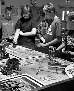 From left: Silas Riley, Allan Gibson, Michael Hardesty and Ben Dunz demonstrate different aspects of their robotic field map. Holding a Lego plastic bag, Gibson explained that a simple bag could pose a number of problems during competition – such as jamming equipment and threatening marine life. Photo courtesy of C. Moore