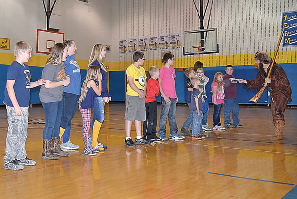"""West Virginia University Mountaineer Michael Garcia, right, leads Green Bank Elementary-Middle School students in a mini-tryout to be the school's honorary Mountaineer. The contest included students giving their best yell and leading the crowd in cheering """"Let's Go, Mountaineers."""" Alexa Taylor was named the winner. Garcia visited all five schools in the county Thursday. S. Stewart photo"""