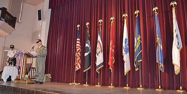 Pocahontas County Veterans Honor Corps commander Rick Wooddell, at podium, and Honor Corps member Willard Pingley perform the POW/MIA ceremony at the Veterans Day Dinner Wednesday at the Pocahontas County Opera House. The stage was adorned with flags from each branch of the military, the POW/MIA flag, West Virginia Flag and United States Flag. S. Stewart photo