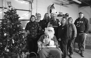 """The Pocahontas County Animal Shelter staff and volunteers gather around Santa Claus at their holiday open house December 21. From left to right: Linda Thompson, Teresa Teter, Rhonda Day, Jesse Blake, Clarence """"Lucky"""" Perry, Robby Long, Chip Adkins, Stephanie Long and shelter manager Robin Robertson. Buster, a former shelter dog adopted by Teter, is seated on Santa's lap. Not pictued: Jenna Bennett and Josh Vaughan. Photo courtesy of Cailey Moore"""