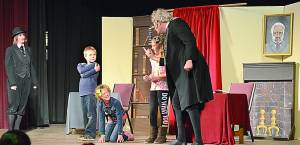 Hannah Redmond's Bob Cratchit and the other apprentices look on as Kyle Walter's Ebenexer Scrooge asks Danielle Yingling why she's kneeling on the ground. In an attempt to keep Scrooge from seeing her pink shoe, Yingling said she was looking for money. C. Moore photo.