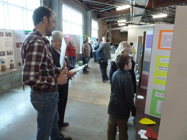 Students filled the basement of the National Radio Astronomy Observatory Science Center with creative projects for the county Science Fair last week. Above, a duo presents their project to the judges. Photo courtesy of Kathryn Williamson