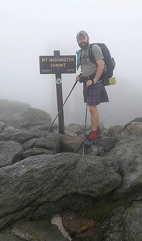 In the fog of a New Hampshire morning, Hillsboro native Mathias Callison takes a moment to pose beside the sign at the Mt. Washington Summit on the Appalachian Trail.  Photo courtesy of Mathias Callison