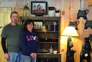 Greg and Kristie Church stand in front of  one of the many pieces of cabinetry handcrafted by Greg for their 4th Avenue Mason Jar Trading Post. The couple works together to create each piece – Greg builds and distresses, while Kristie paints and stains.  C. D. Moore photo