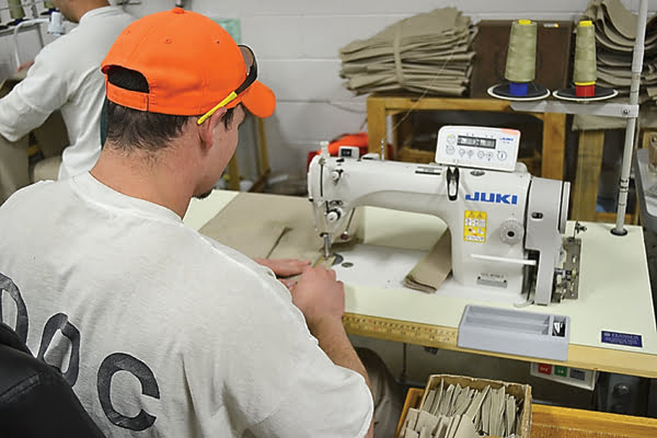 An inmate at Denmar Correctional Facility adds pockets and seams to a pair of inmate pants in the sewing industry section of the facility. Up to 50 Denmar inmates work in the sewing department, making inmate uniforms for all of the prisons in West Virginia. S. Stewart photo