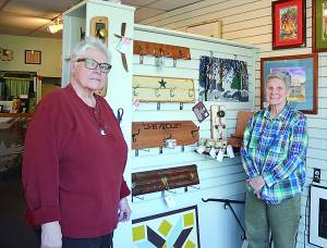 Sarah Moss, left, and Dianne Monroe, right, stand with a display of their work. One of Monroe's driftwood crosses hangs beside a key holder made from reclaimed wood and an old door knob, while examples of their coat racks and Moss' love boxes are to the right. C. D. Moore photos