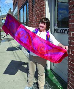 STEPPING OUTSIDE THE 4th Avenue Gallery in Marlinon, Kathy Henry, right, takes advantage of the sunshine to show the vibrant colors in one of her scarves. Rather than purchasing pre-mixed dyes, she prefers to mix her own colors and is known for creating beautiful, intense colors that pop.