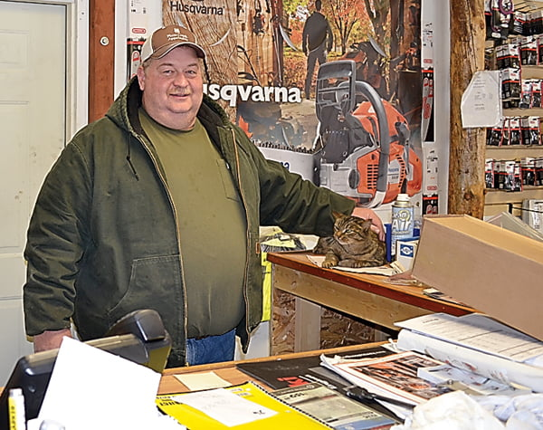 "Durbin resident and businessman Kenneth ""Buster"" Varner has expanded his business from just Varner's Construction Company to nearly a dozen businesses in the past 33 years. Here, Varner takes a break at the auto parts store to visit with the office cat. S. Stewart photo"