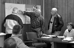 JOE SMITH, LEFT, and councilmember Don Morrison, right, look on as Mayor Sam Felton draws a map to show the potential location of the Frank Gravely Memorial Flag Pole planned for Mountain View Cemetery. C. D. Moore photo
