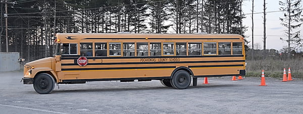 BUS DRIVERTRAINER Jimmy Ryder puts potential substitutes behind the wheel as they learn the ins and outs of driver safety. The training also includes various obstacle courses. Above, bus driver trainee Evan Rose expertly backs a school bus into the designated area at the Green Bank school. S. Stewart photo