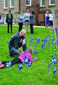 Tim Sacca digs tiny holes for his daughter, Emma, as she places pinwheels on the lawn of the Pocahontas County Courthouse. The whimsical pinwheels are reminiscent of childhood and are used to capture the attention of community members in the hopes of preventing future child abuse. The pinwheels will remain on the lawn until May 2. C. D. Moore photo