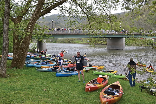 a crowd ON the bridge at Marlinton cheers for the racers as they rush their kayaks and canoes for the second leg of the Great Greenbrier River Race triathlon Saturday. After a three mile run, racers take a four-mile ride down the river before returning to Marlinton in a 10-mile bike ride from Buckeye.  S. Stewart photo
