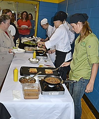 Green Bank Elementary-Middle School volunteers were treated last week to a brunch prepared by Pocahontas County High School ProStart students. From right:Brittney Sharp, ProStart teacher Teresa Mullen, Courtney Cohenour and Tara Warner prepare brunch staples including custom omelets and Bananas Foster. S. Stewart photo