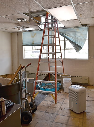 Kiddie pools, buckets and trash cans catch rain water in a room at the Board of Education office where heavy rain caused a major leak in the roof. S. Stewart photo