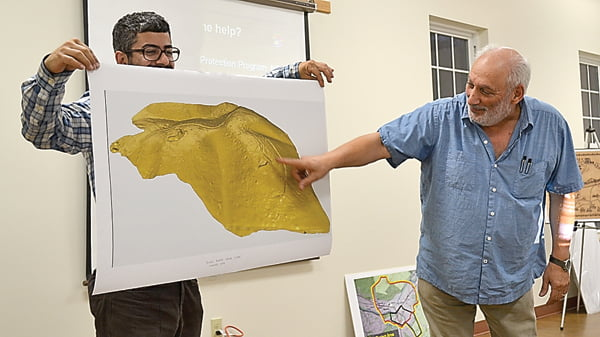 At the Camp Bartow preservation meeting, team leader Mike Gioulis, right, explains the laser scan map of the Warner property across from the Traveller's Repose in Bartow. The map, held by Gabe Hopen, reveals trenches, tent sites and two cannon locations. S. Stewart photo