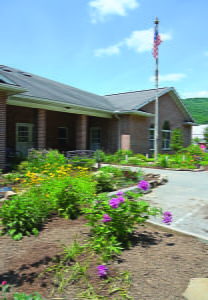 LIBRARY PATRON TRISH McNaull and volunteers from the Pocahontas County Day Report Center and Drug Court have been working diligently to revamp the front of McClintic Public Library. Using an array of annual and perennial flowers, McNaull has transformed the previously lackluster landscaping into a colorful garden in memory of Ina Montgomery. Final touches, such as reinstalling the freshly painted picket fence around the flag pole and adding a memorial plaque to the wooden bench in the garden, will warmly welcome Ina's friends and library patrons . C. D. Moore photos