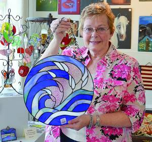 JUDY GUM BEGAN working with stained glass four years ago. What was once an item on her post-retirement bucket list quickly became a hobby, and according to Gum, her hobby has since evolved into an addiction. The panel Gum is holding is just one of many new pieces she added to the 4th Avenue Gallery Friday afternoon.