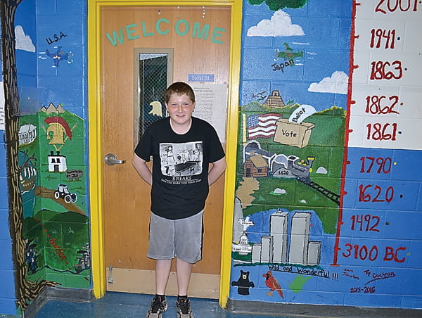 Green Bank Elementary-Middle School seventh grader Ty Cochran stands next to the history mural he painted on the wall near Amanda Nottingham's classroom. Along with featuring major historical events, the mural has a legend showing the year those events took place. S. Stewart photos