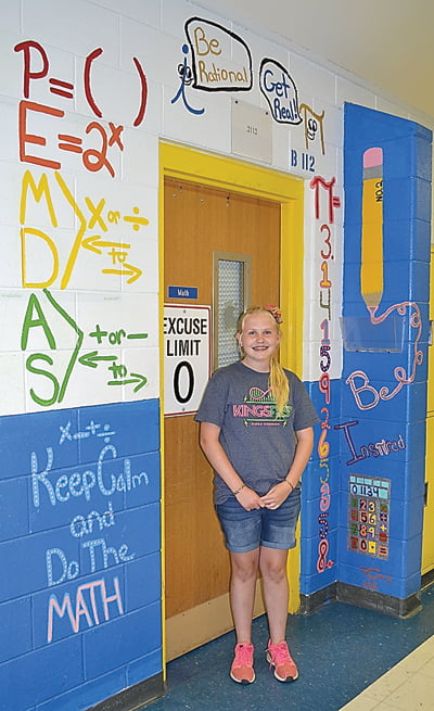 Seventh grader Sienna Bircher and her math mural at the entrance to Julie Brown's classroom. Bircher used bright colors, mathematical puns and equations to make her mural fun.