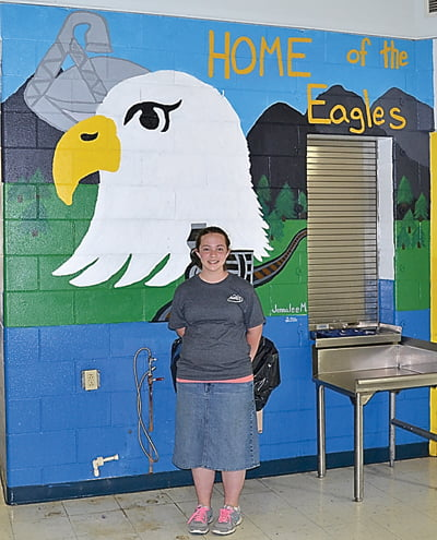 Seventh grader Jennalee Meck's mural was inspired by Green Bank and features of the surrounding area, including the Cass train and Green Bank Telescope. Her mural is on the wall in the cafeteria.