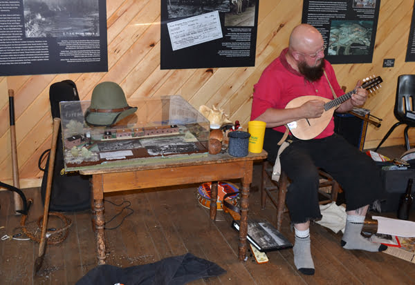 Sitting among his collection of logging artifacts and a model of a West Virginia logging town, Rich Pawling, of Rich Pawling History Alive!, plays mandolin as he sings a Ralph Stanley song during the Cass Logging Days Sunday. Pawling told the history of wood hicks and life in logging towns like the one at the former town of Spruce near Cass. S. Stewart photo