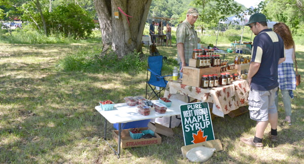 Joining the ranks of Marlinton, Linwood and Snowshoe, Cass is the newest location for the Pocahontas County Farmers Market. Three vendors shared their wares with visitors Saturday. Above, John Wayne helps customers choose a maple product produced at Frostmore Farm. S. Stewart photo