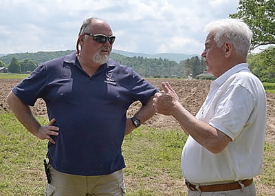 NRAO Business Manager Mike Holstine and West Virginia Agriculture Commissioner Walt Helmick discuss the potato project on-site last week as planters complete the planting process in the field behind them.