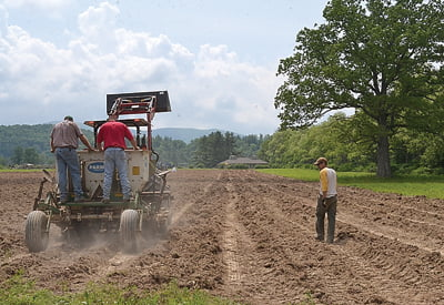 Bartow resident Jonah Bauserman, right, walks alongside the potato planter. As Jarrett McLaughlin and Jay Saville monitor the potatoes from the back of the  planter, Bauserman watches to make sure the equipment is operating properly.