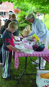 The pioneer-themed arts and crafts demonstrations drew a lot of attention over the weekend. At the quill and ink station, Margaret Worth sets out colored ink while kids use quills to practice their drawing skills. C. D. Moore photo