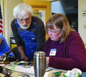 INSTRUCTOR AND ARTIST David Houser observes the progress of student Sue Shearer as she works on her Dresden Plate stained glass piece.