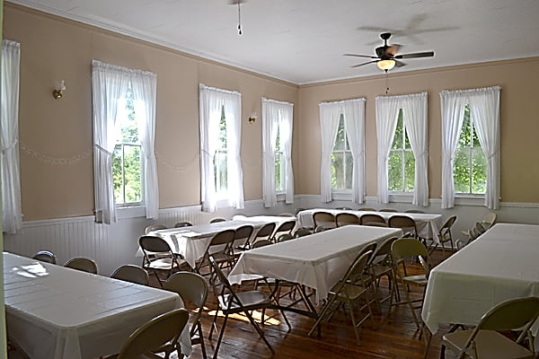 The main classroom of Campbelltown School was remodeled to be used as a dining hall or meeting hall. Natural light spills in through the multiple windows lining two walls of the building. Although it is not air conditioned, the windows and ceiling fans cool the former school. S. Stewart photo