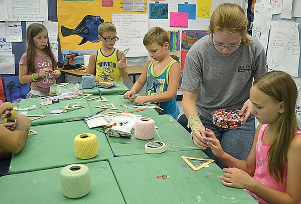 At the Energy Express Open House, Tessa Himelrick helped students make triangular dreamcatchers with popsicle sticks, string and beads. S. Stewart photos