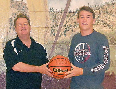 Pocahontas County High School basketball coach Tim McClung, left, presents 2016 grad JD Hensler with a 1,000 point basketball. Hensler ended his career as a Warrior with a total of 1,033 points. S. Stewart photo