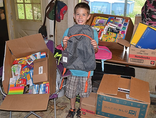 Rising Green Bank Elementary-Middle School sixth grader Gage Wilson stands among the school supplies he collected in the past month for children affected by the recent devastating flood in Greenbrier County. S. Stewart photo