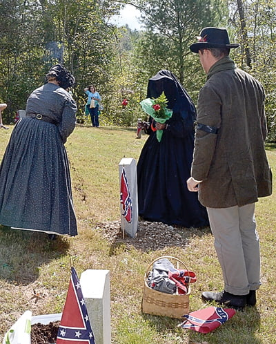 Members of the Tennessee Order of Confederate Rose attended Huntersville Traditions Day Saturday to honor four Civil War Confederate soldiers with a grave stone placement ceremony. Above, Vonda Dixon, left, sprinkles Georgia dirt on the grave of Private David R. Dodd, Company E, 14th Georgia Infantry as fellow mourners watch. S. Stewart photo