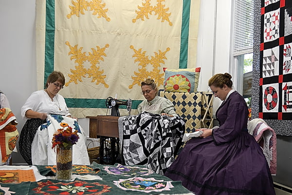Crafters shared their talents in the old Huntersville School cafeteria. The room was decorated with colorful quilts – new and old. From left, Cheryl Taylor-Dean, Sandy Irvine and Erin Lore concentrate on the quilts they are working on as visitors pass through the room. S. Stewart photo
